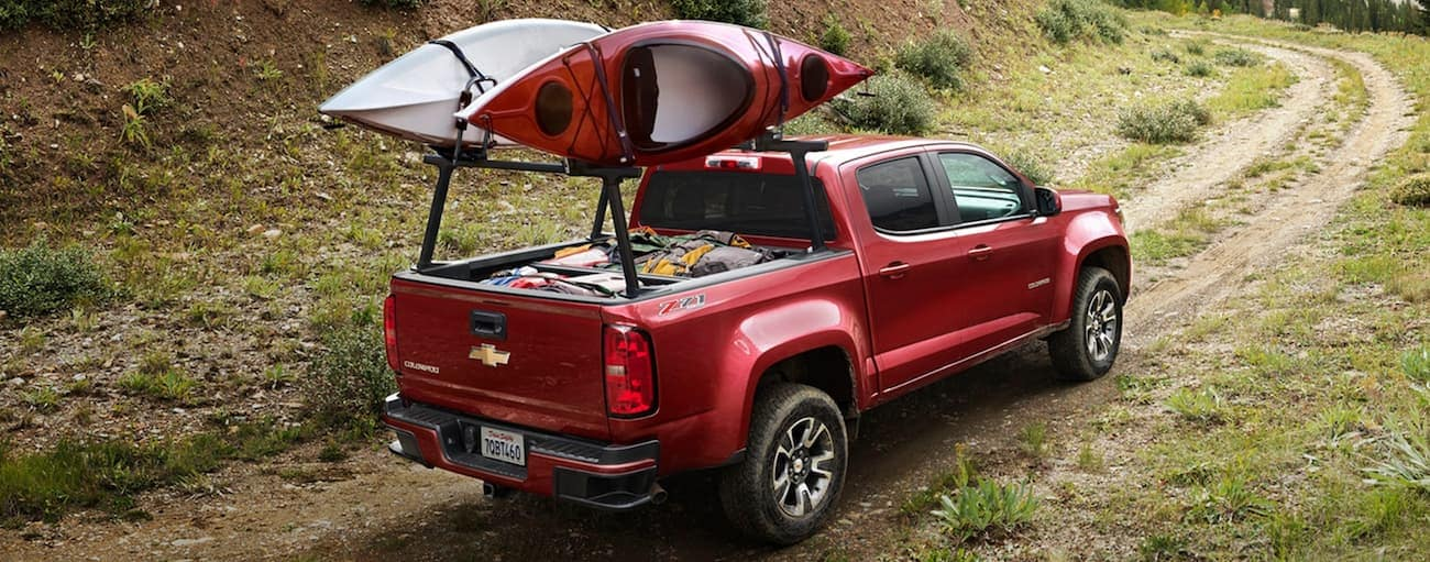 A red 2020 Chevy Colorado, which wins when comparing the 2020 Chevy Colorado vs 2020 Ford Ranger, is driving on a dirt trail with kayaks on the bed rails.
