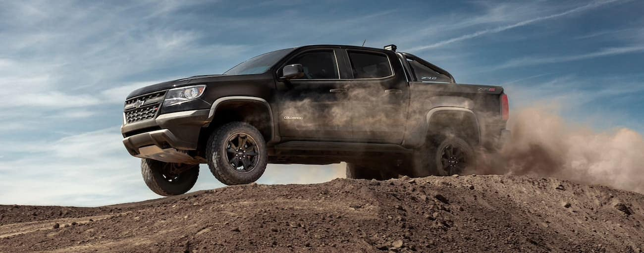 A black 2020 Chevy Colorado is jumping a dirt mound while off-roading near Albany, NY.