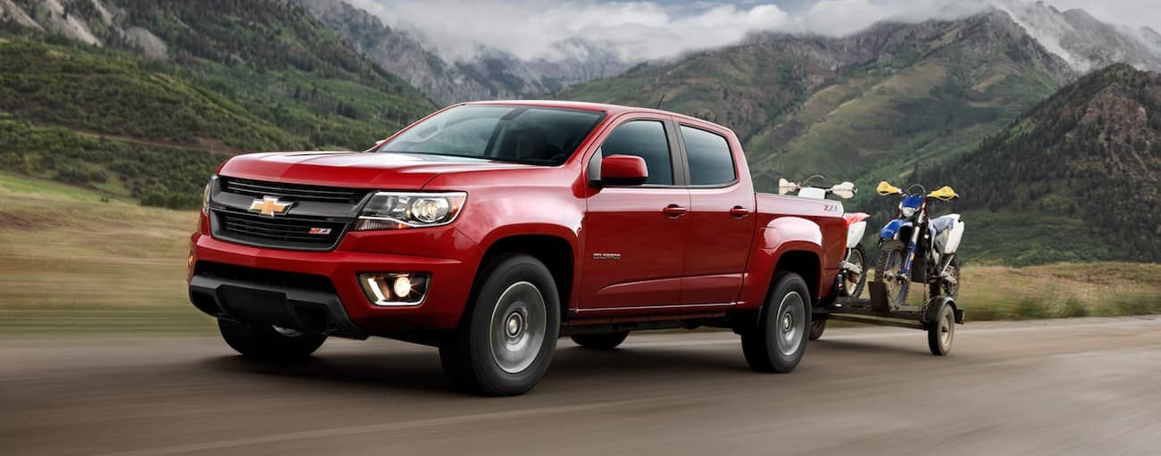 A red 2020 Chevy Colorado, which wins when comparing the 2020 Chevy Colorado vs 2020 Toyota Tacoma, is towing dirt bikes past mountains.