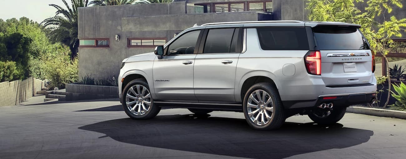 A silver 2021 Chevy Suburban is parked at a modern grey house.
