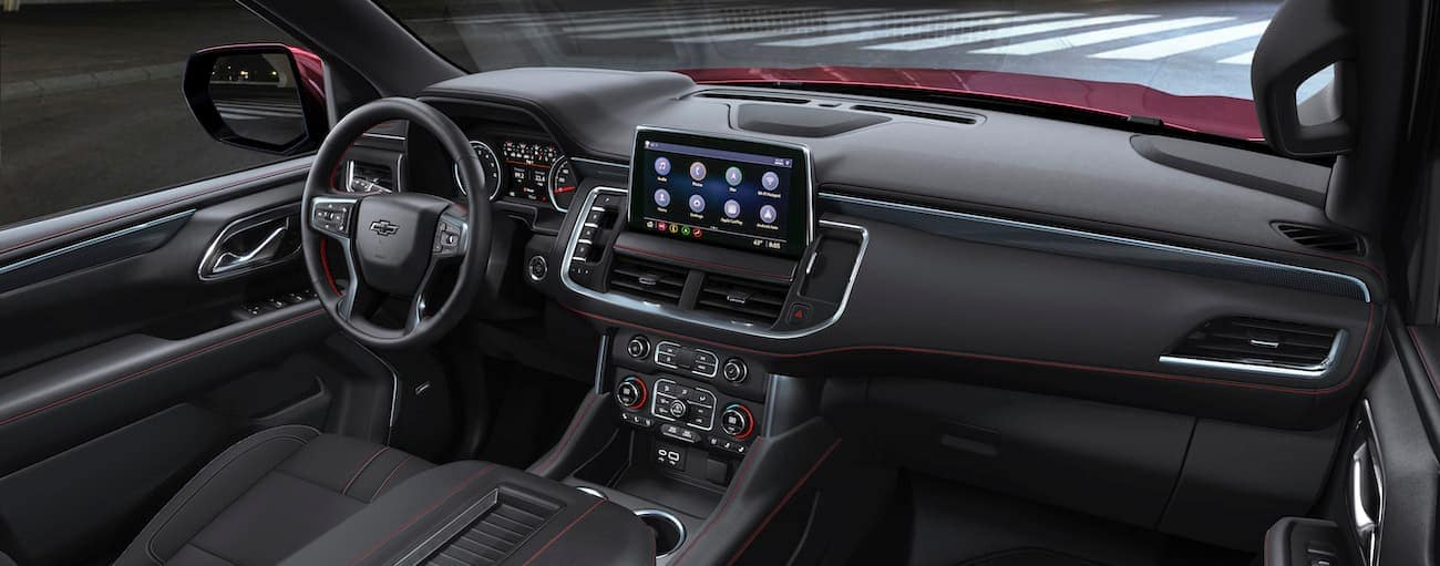 The dashboard of a 2021 Chevy Tahoe is shown with an Albany, NY, street in the window.