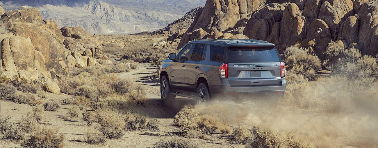 A grey 2021 Chevy Tahoe Z71 is off-roading on a desert trail.