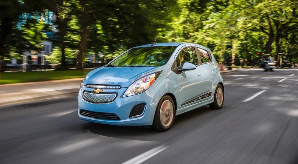 A short-lived hybrid Chevy car, a light blue 2015 Chevy Spark EV is driving on a road near Albany, NY.
