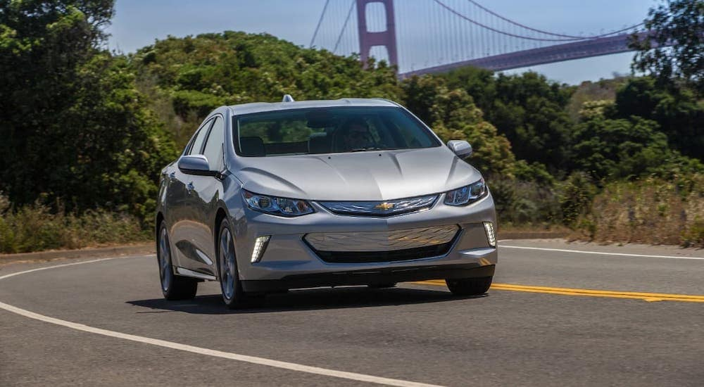 A silver 2019 Chevy Volt plug-in hybrid is driving on a road with a bridge in the distance.