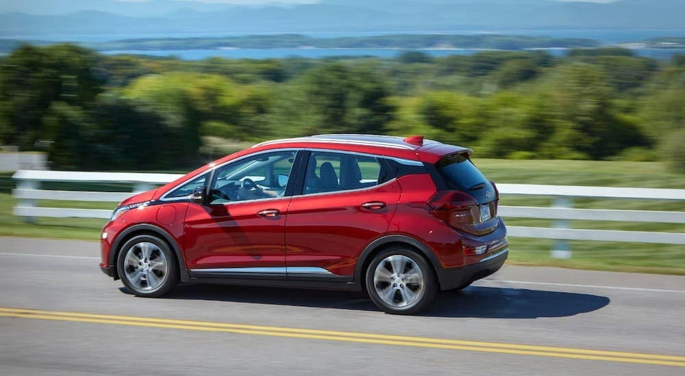 A red 2020 Chevy Bolt EV is driving on a highway near Albany, NY.