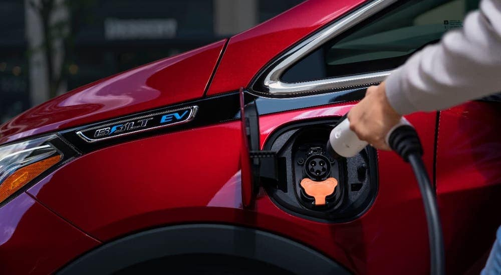 A hand is charging a red 2020 Chevy Bolt EV at a Chevy dealership near Clifton Park, NY.