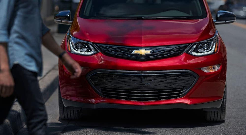 A red 2020 Chevy Bolt EV is shown from the front, parked on a street in Clifton Park, NY.