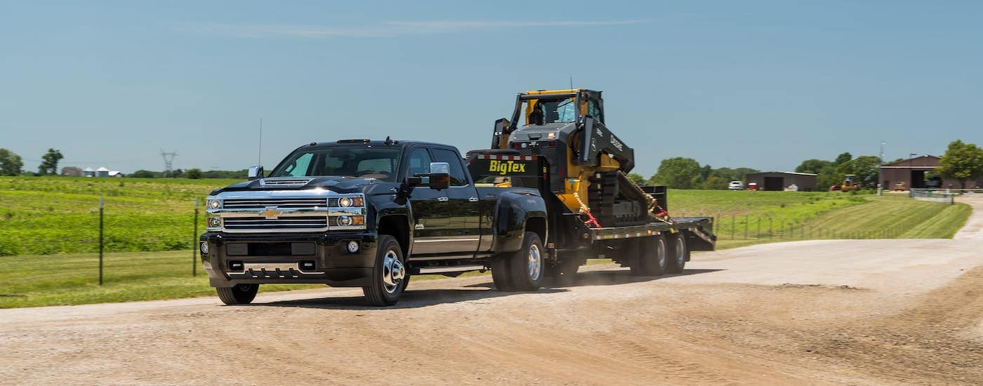 A black 2017 Chevy Silverado 3500HD is towing construction equipment past a farm.