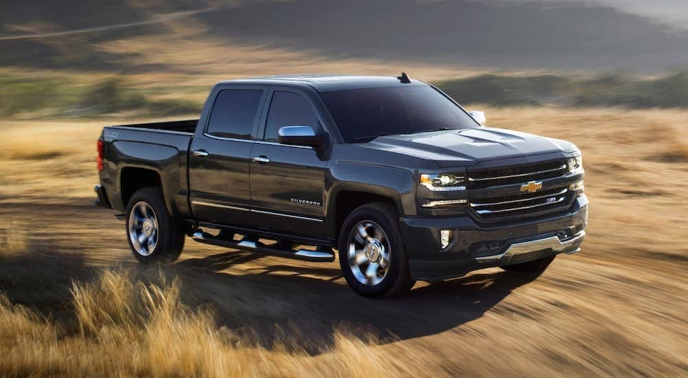 A black 2018 Chevy Silverado 1500 Z71 is driving on a dirt trail.