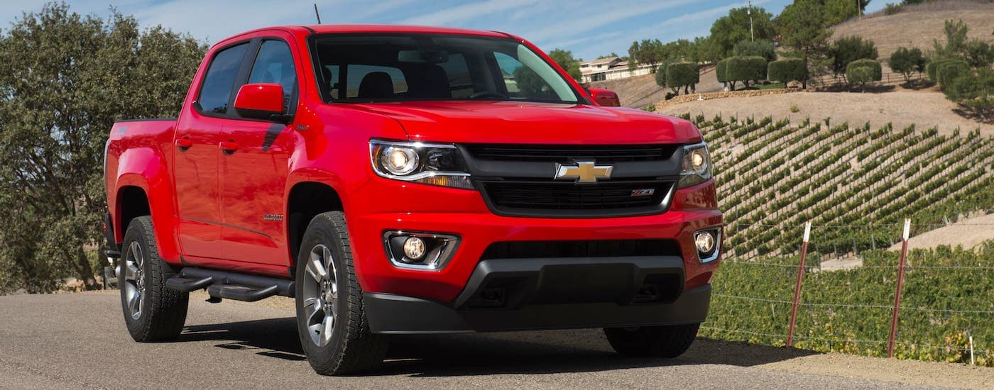 A popular used Truck in Albany, NY, a red 2019 Chevy Colorado is shown parked in front of a winery.