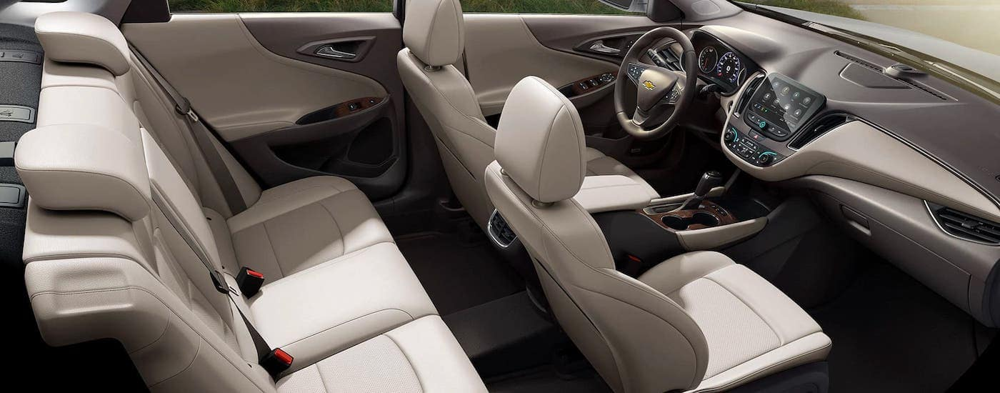 The white interior rows of seats are shown from a high angle in a 2020 Chevy Malibu.