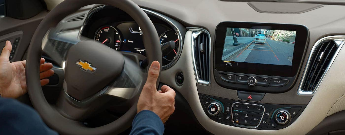 The infotainment screen and steering wheel are s shown while the Automated Parking feature is in use.