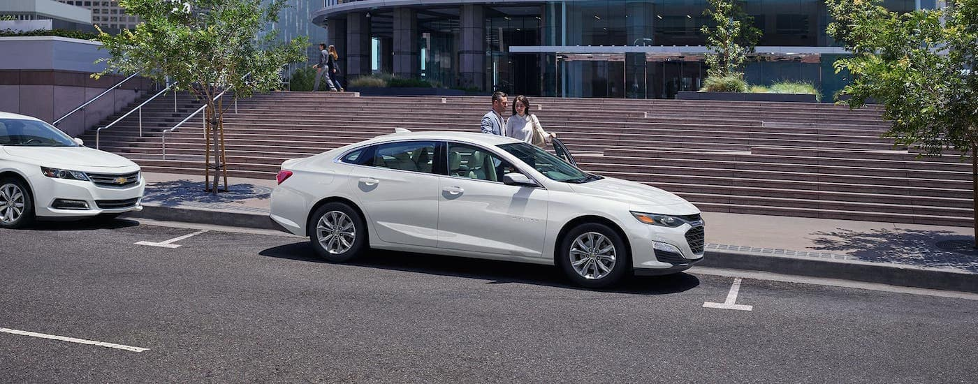 A smiling couple is about to get into a 2020 Chevy Malibu which is parked on a street near Albany, NY, and just won the 2020 Chevy Malibu vs 2020 Nissan Altima comparison.