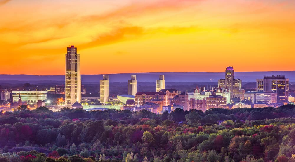 Albany NY skyline behind orange and red fall trees and in front of an orange sky