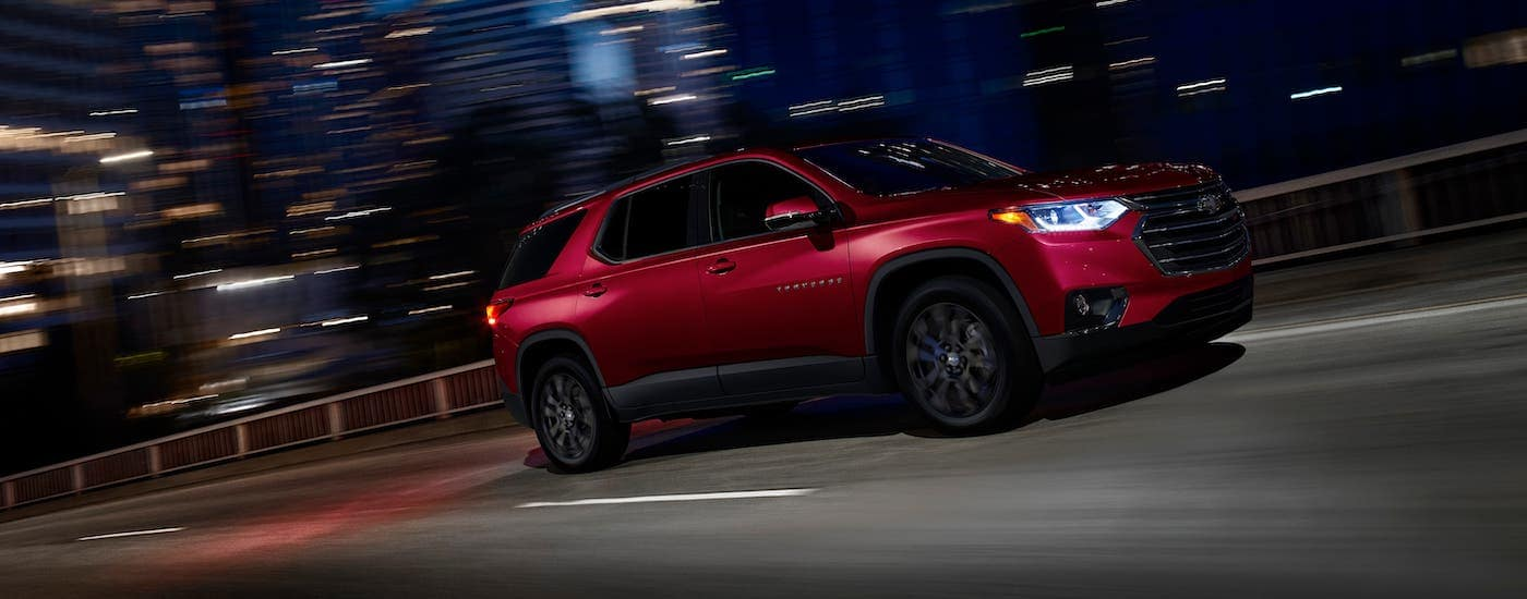 A red 2020 Chevy Traverse RS is driving on a city street at night after winning the 2020 Chevy Traverse vs 2020 Kia Sorento comparison.