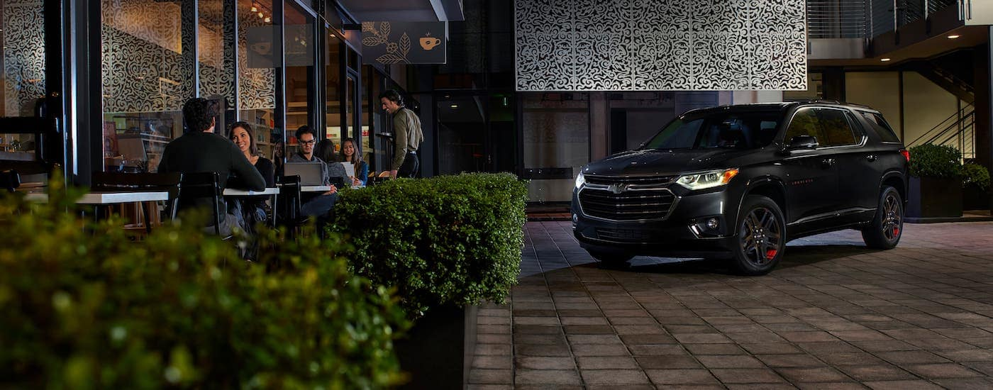 A black 2020 Chevy Traverse Red Line Edition is parked outside an Albany, NY, restaurant at night.