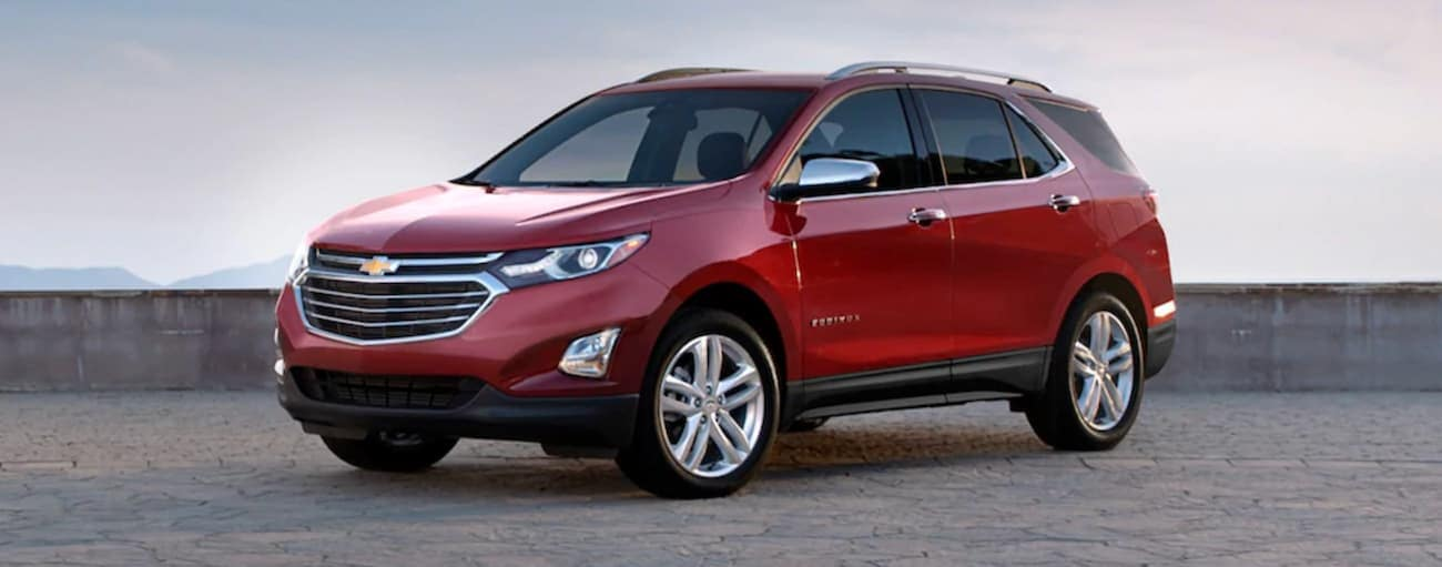 A red 2020 Chevy Equinox is parked in front of a low cement wall after winning the 2020 Chevy Equinox vs 2020 Hyundai Santa Fe comparison.