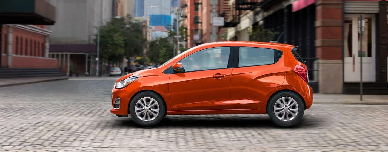 An orange 2021 Chevy Spark is shown from the side on a cobble city street.