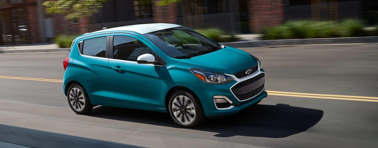 A teal and white 2021 Chevy Spark is driving on a city street near Albany, NY.