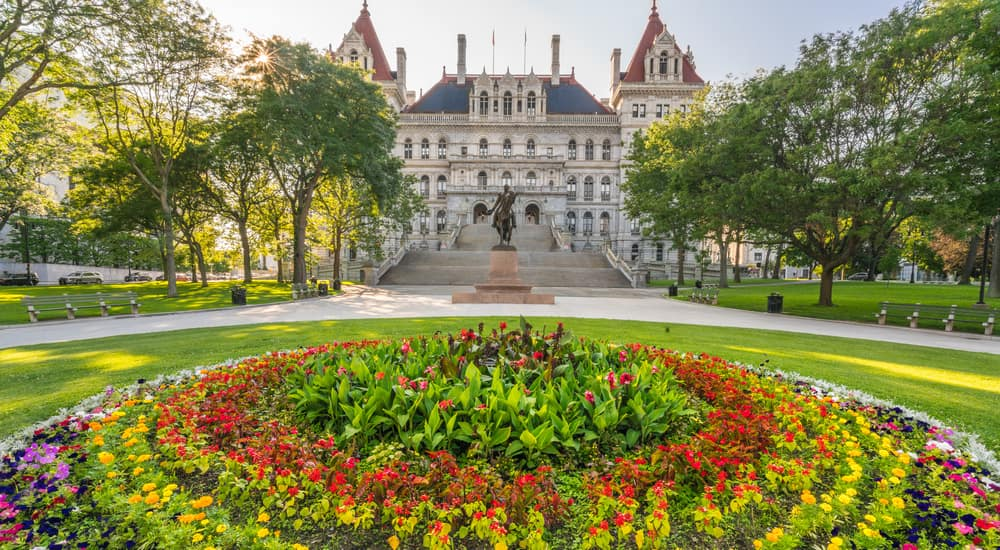 Circular bed of flowers in front of the tall, stone, New York state building in Albany