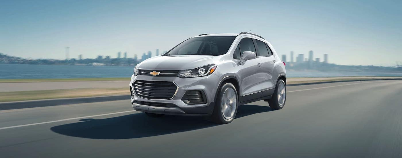 A silver 2021 Chevy Trax is driving away from a city on a highway.