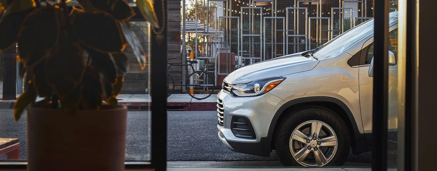 The front half of a white 2021 Chevy Trax is shown through a houses window.