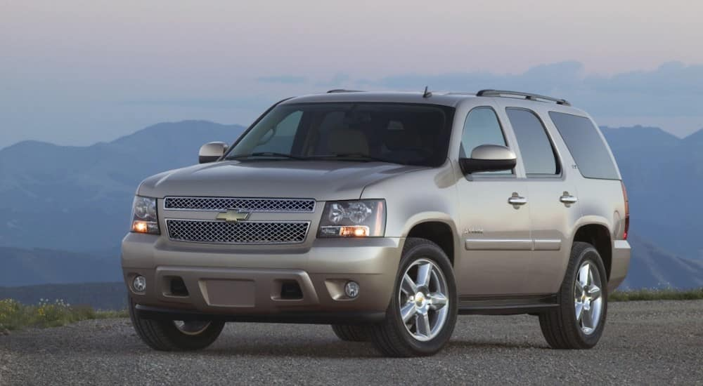 Tan 2009 Chevrolet Tahoe parked on pavement in front of tall mountains