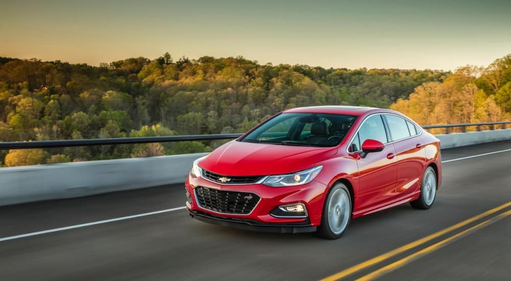 Red 2016 Chevrolet Cruze sedan driving down a paved road next to a guardrail and trees