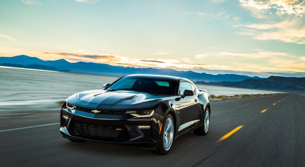 Black 2017 Chevrolet Camaro driving down a paved road next to a body of water and mountains
