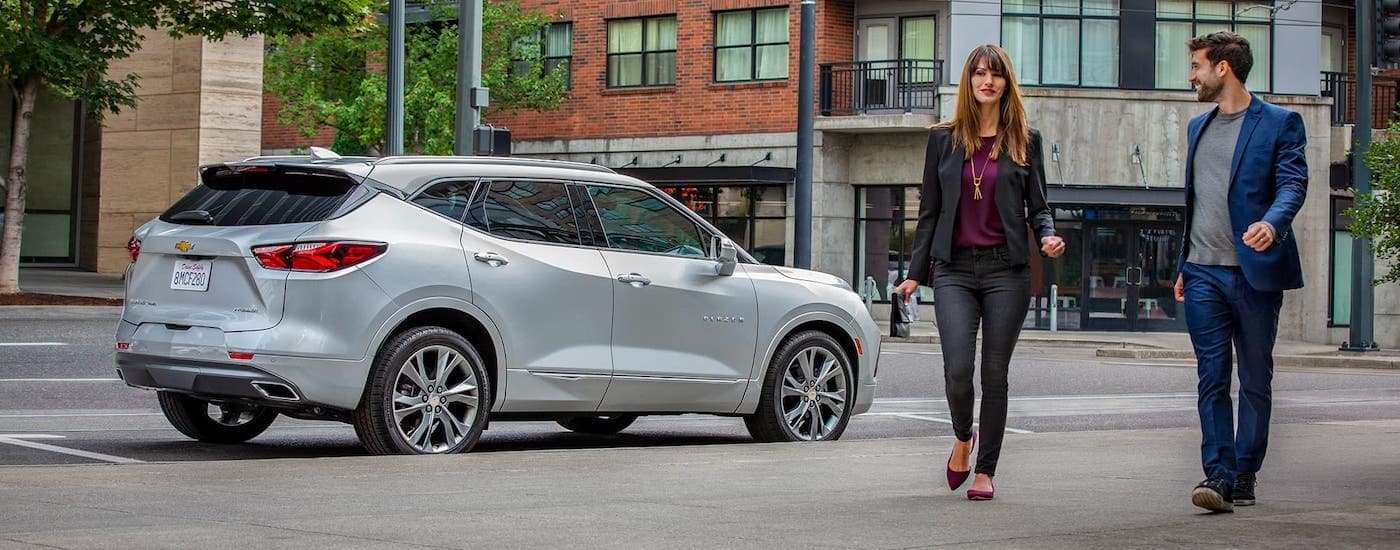 A well-dressed couple is walking away from a silver 2021 Chevy Blazer which is parked on a city street.