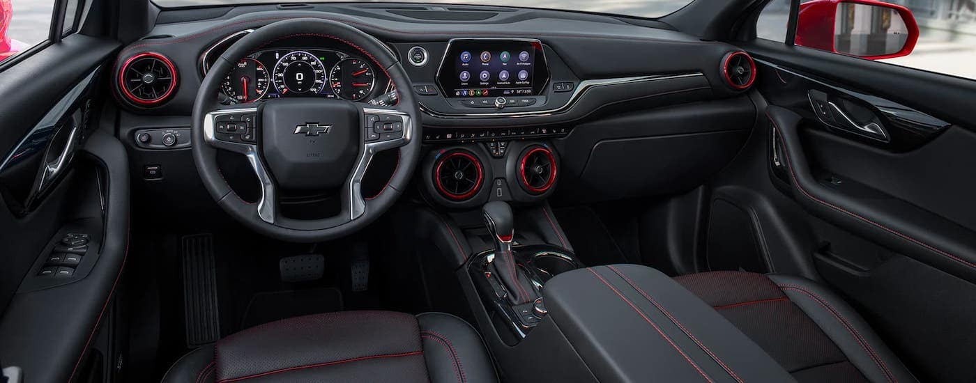 The black interior of a 2021 Chevy Blazer is shown with red accents.