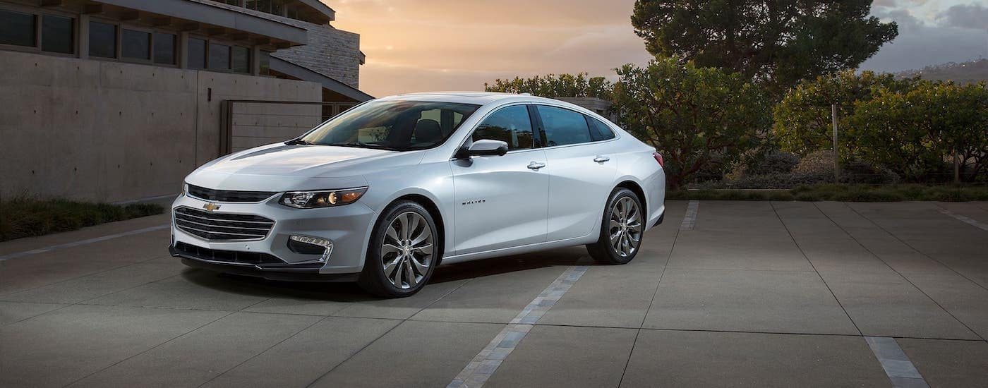 A white 2021 Chevy Malibu is parked in front of a modern home at sunset.