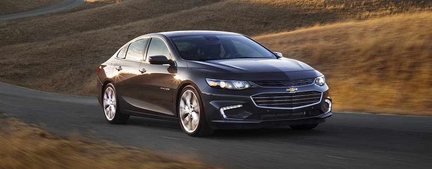 A black 2021 Chevy Malibu is driving on a highway past yellow hills.