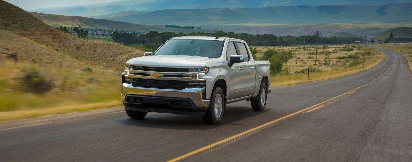 A silver 2021 Chevy Silverado 1500 LT is driving on an empty highway.