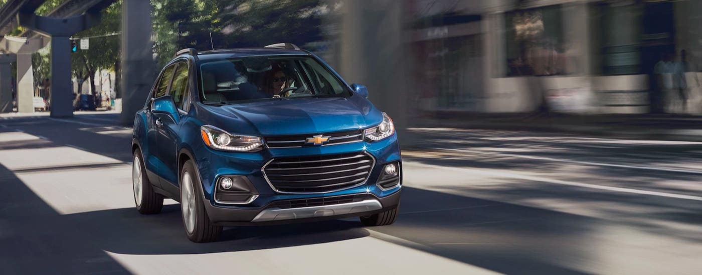 A blue 2021 Chevy Trax is driving under a bridge.
