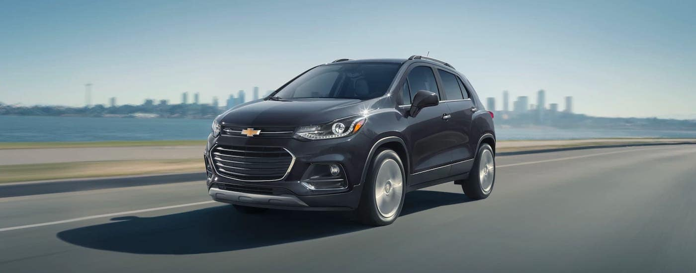 A black is driving away from a city after winning the 2021 Chevy Trax vs 2021 Buick Encore comparison.
