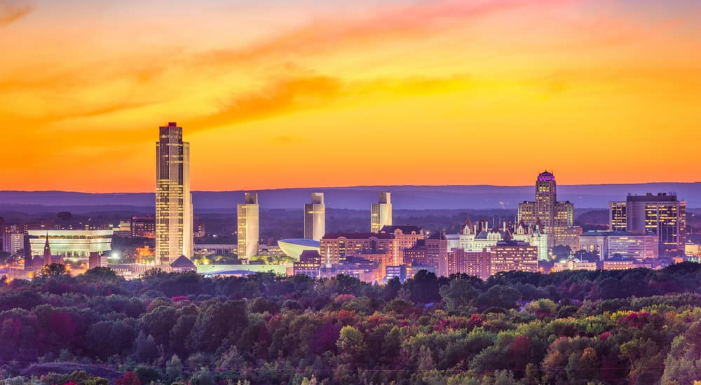 Colorful trees and the Albany NY skyline in front of an orange sky