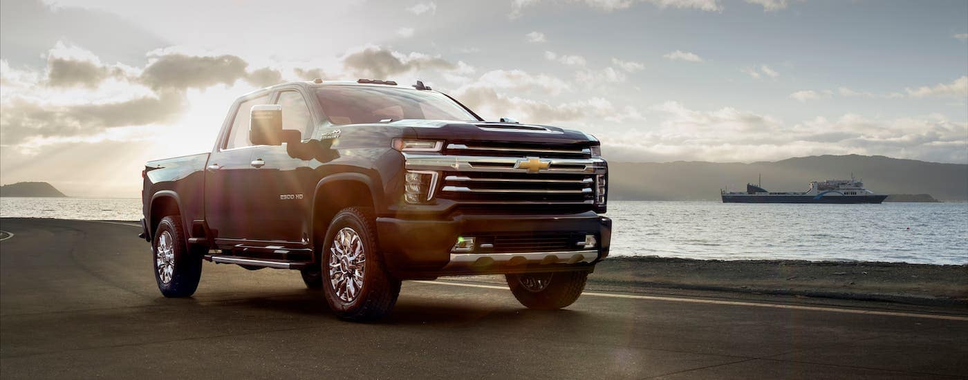 A black 2021 Chevy Silverado 2500HD High Country is parked in front of a river.