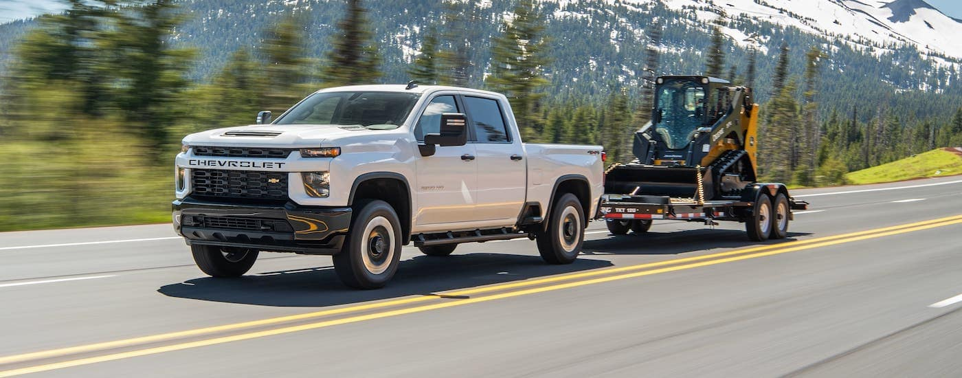 A white 2021 Chevy Silverado 2500HD is towing construction equipment on a highway in front of evergreen trees and mountains.