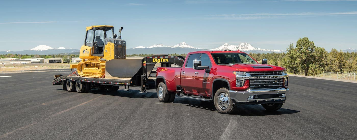 A red 2021 Chevy Silverado 3500HD with a trailer and construction equipment is parked on an empty road.