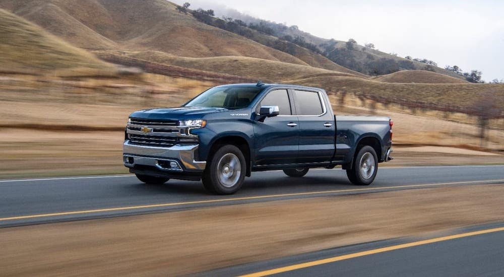 A Chevy diesel truck for sale near you, a blue 2021 Chevy Silverado 1500, is driving on a road past hills.