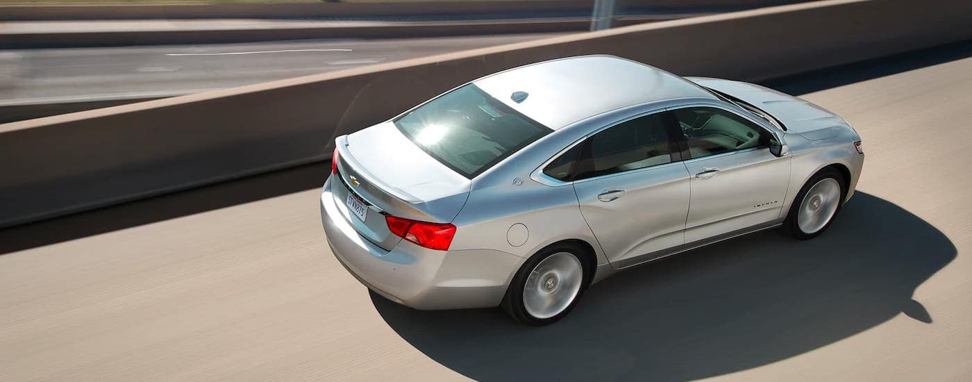 A silver 2020 Chevy Impala is shown from a high angle driving on a highway.