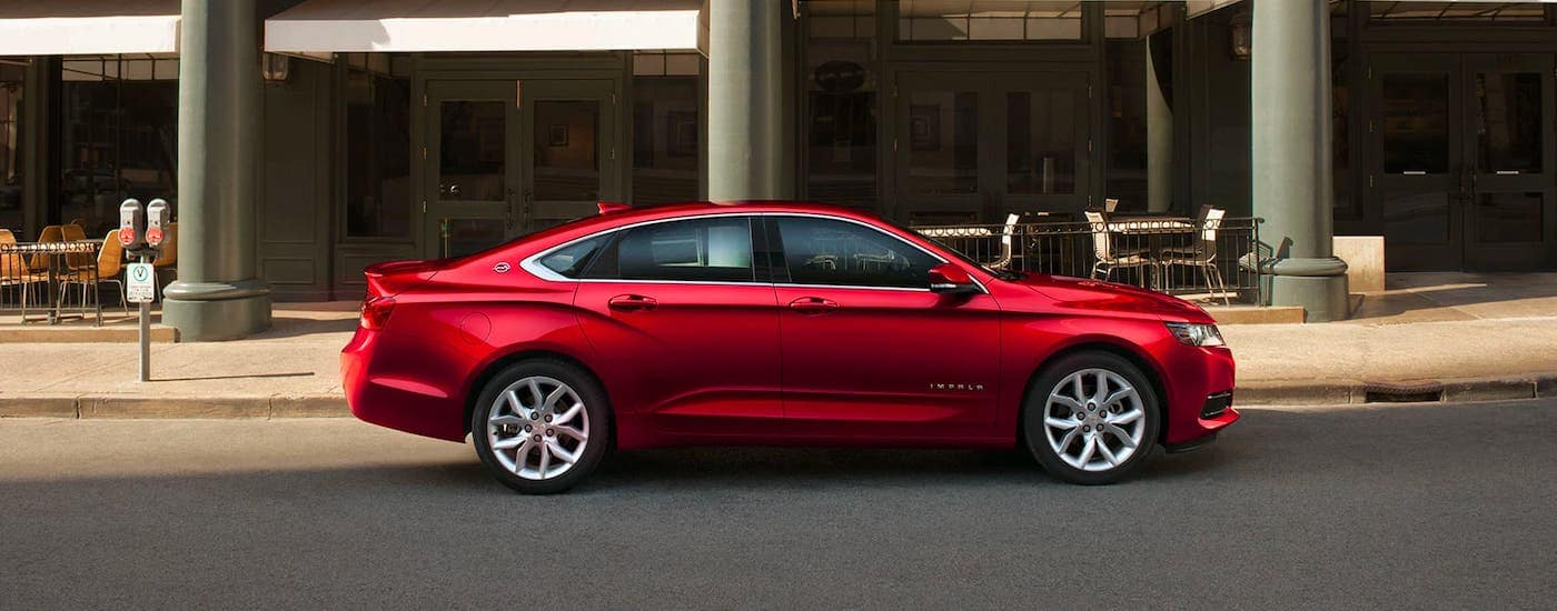 A red 2020 Chevy Impala is shown from the side while parked in front of a cafe.