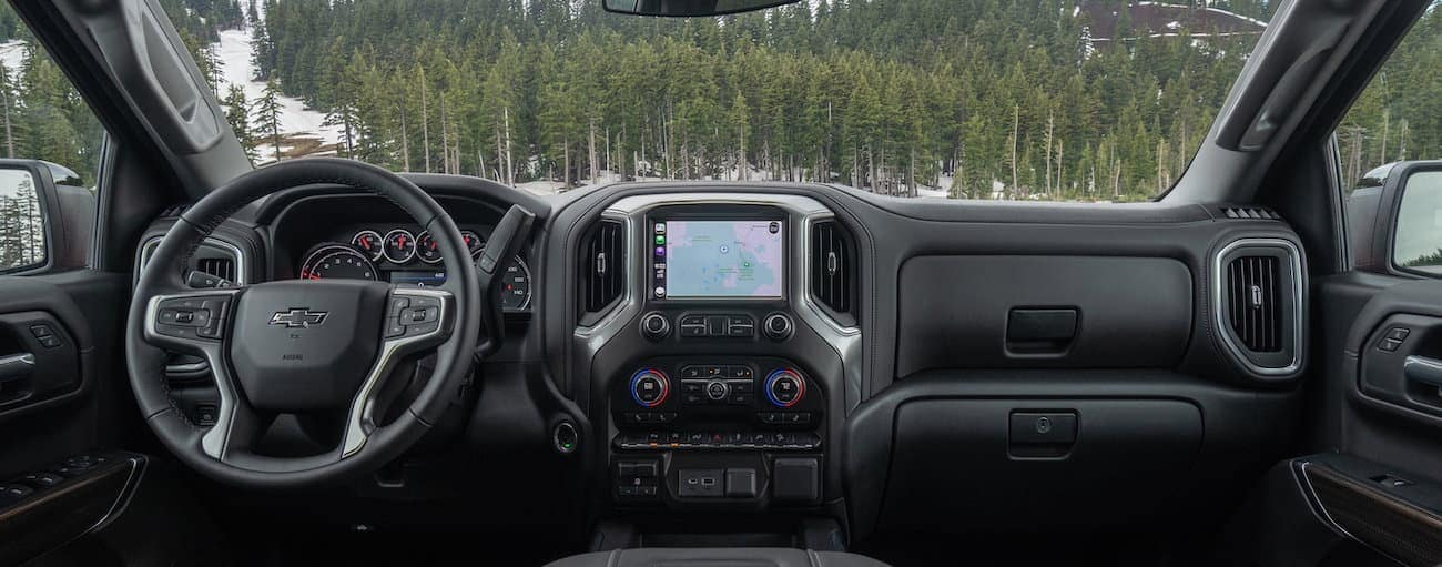 The dashboard and infotainment screen in a 2021 Chevy 1500 are shown with pine trees in the windshield.