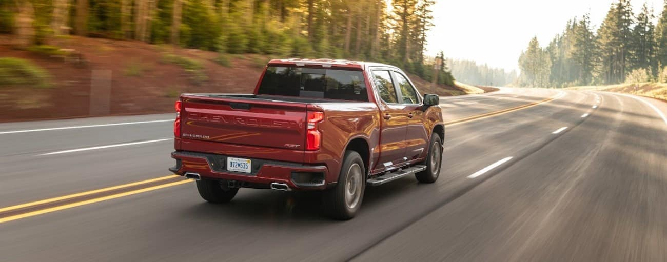 A red 2021 Chevy 1500 diesel is driving on a multi-lane road past pine trees after winning the 2021 Chevy 1500 diesel vs 2021 Ram 1500 diesel comparison.
