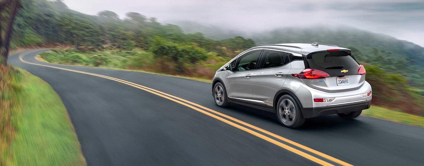 A silver 2021 Chevy Bolt is driving on a misty highway in the mountains.