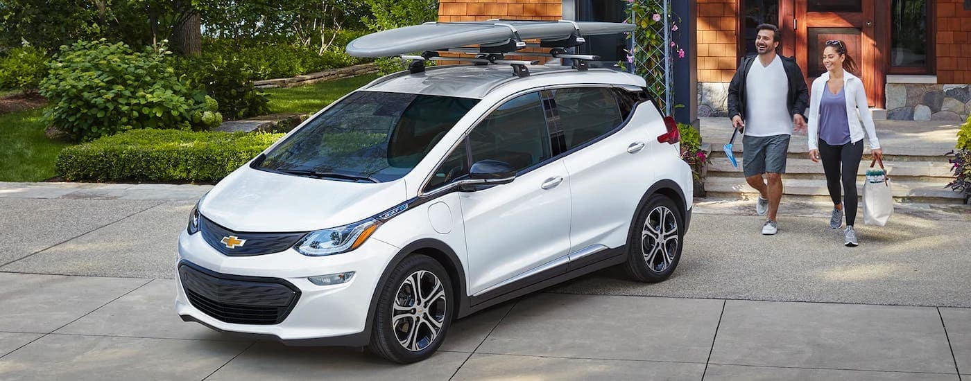 A couple is walking towards a white 2021 Chevy Bolt that has a surfboard on the roof.