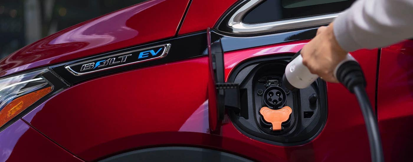 A hand is plugging in a red 2021 Chevy Bolt.