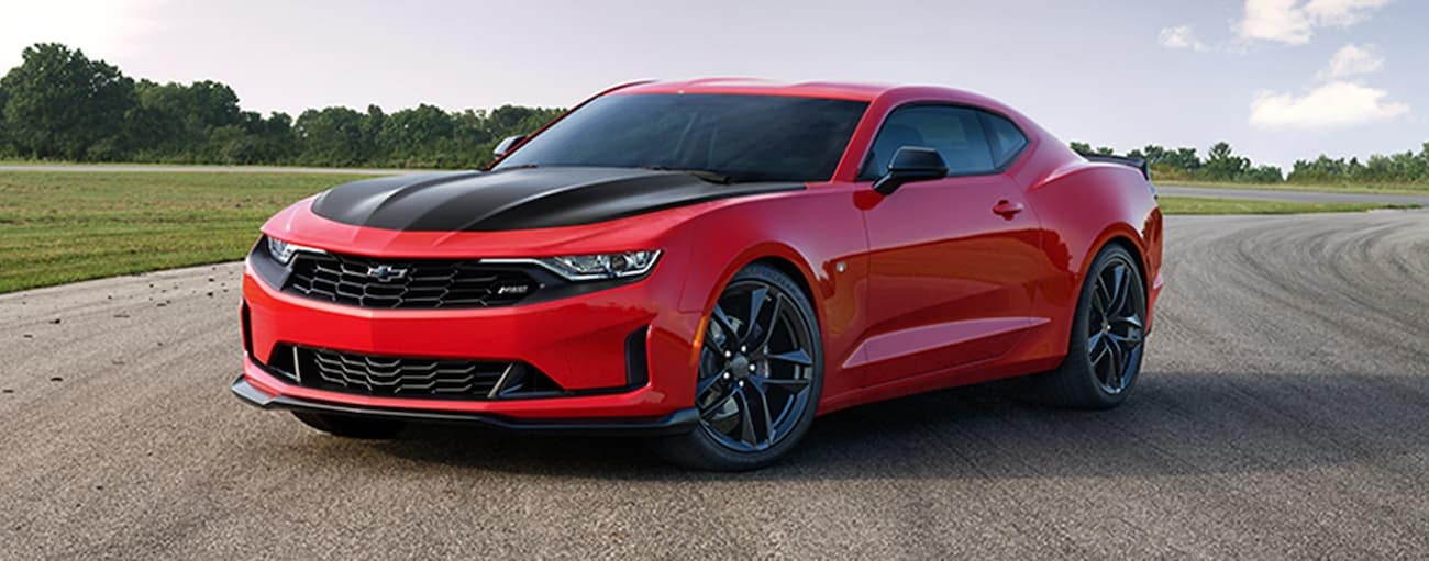 A red 2021 Chevy Camaro with a black hood is parked on a racetrack.