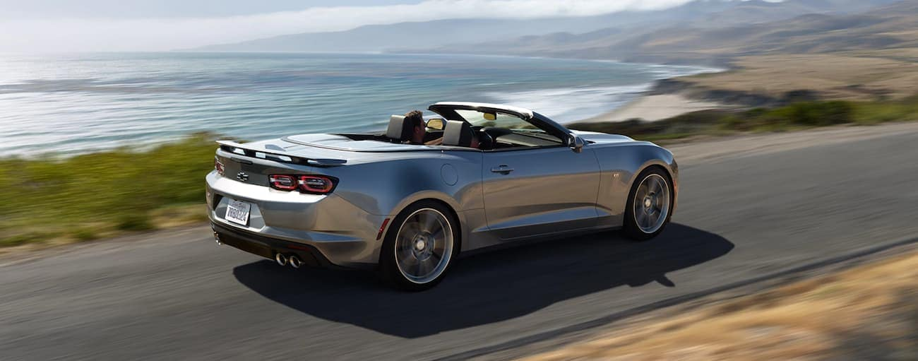 A silver 2021 Chevy Camaro convertible is driving past the ocean after winning the 2021 Chevy Camaro vs 2021 Ford Mustang comparison.